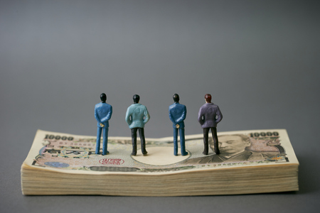 Miniature men with Japanese yen banknotes