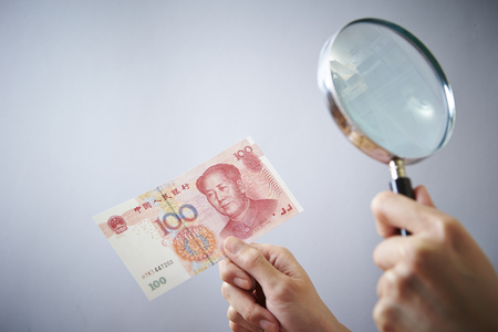Looking at Chinese RMB banknote through magnifying glass