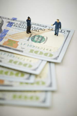 US dollar banknotes with miniature men