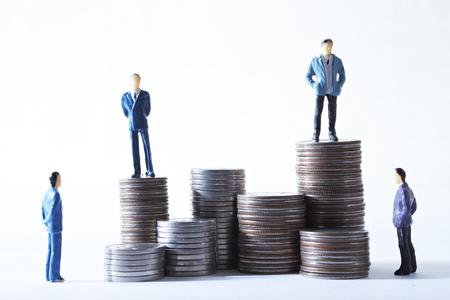 Miniatuur mannen met munten Stockfoto
