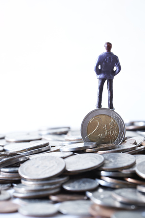 Miniature man with Euro coins Stock Photo
