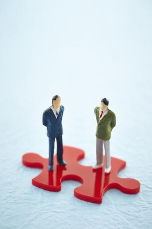 Miniature men on jigsaw puzzle piece