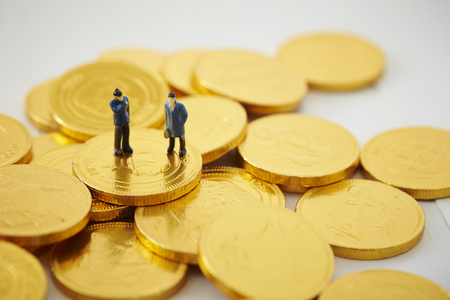 Miniature men with coins Stock Photo