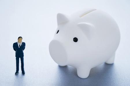 Miniature man with piggy bank