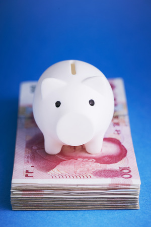 withdrawal: Piggy bank with Chinese RMB banknote