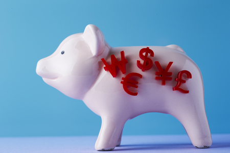 Piggy bank with currency symbols Stock Photo