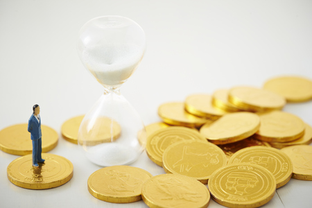 Miniature man with coins and hourglass