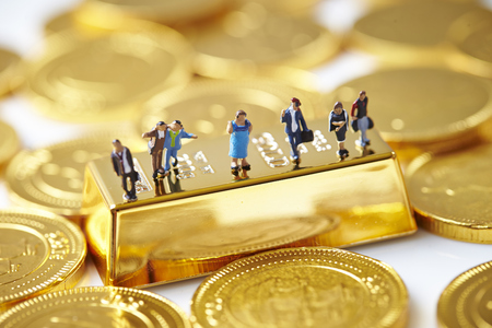 Miniature men with coins and gold bar Stock Photo