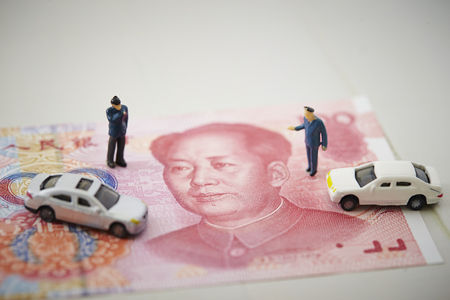 Miniature men with cars and Chinese RMB banknotes