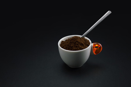 cup of coffee with minced coffee on black background
