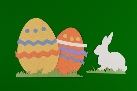 colorful eggs with grass and rabbits drawn and cut on paper, easter egg on a green  background Reklamní fotografie