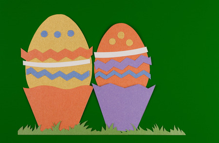 colorful eggs with grass and cut on paper, easter egg on a green background Reklamní fotografie