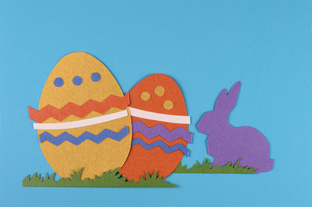 colorful eggs with grass and rabbits drawn and cut on paper, easter egg on a blue background Reklamní fotografie