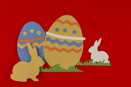 colorful eggs with grass and rabbits drawn and cut on paper, easter egg on a red background