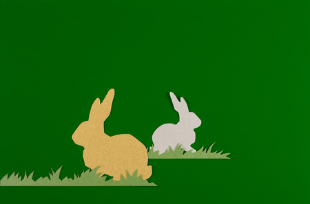colorful rabbits drawn and cut on paper, easter egg on a green background Reklamní fotografie