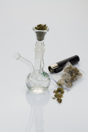beautiful glass pipe with marijuana on white background, with lighter