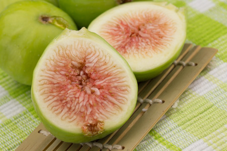 shove: fig fruit on white background with green leaf and shove bamboo over a tablecloth with open fig and red pulp of a biological nature Stock Photo