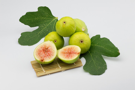 fig fruit on white background with green leaf and shove bamboo over a tablecloth with open fig and red pulp of a biological nature Reklamní fotografie