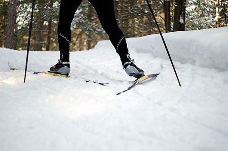 required: Coordination is required for an uphill skate on nordic skis. Stock Photo