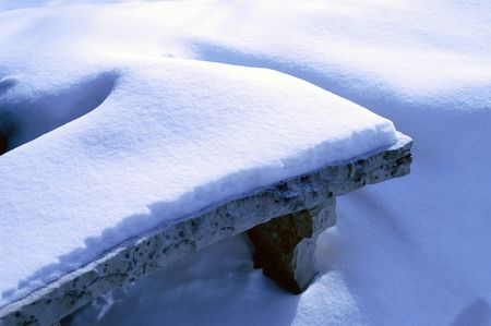 blanketed: Stone bench blanketed in new snow.