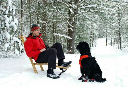 Man and his dog take a break on the trail in Ontario forest. photo