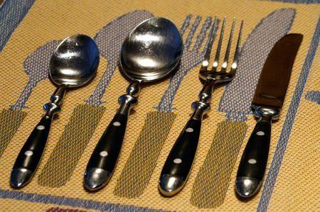 Seeing double. Cutlery set against Swedish linens. Stock Photo - 2665172