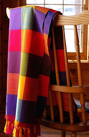 Vibrantly coloured Mexican cloth draped over a combback chair in log home.
