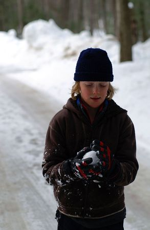 Boy contemplating what to do with his snowball once it is perfected.