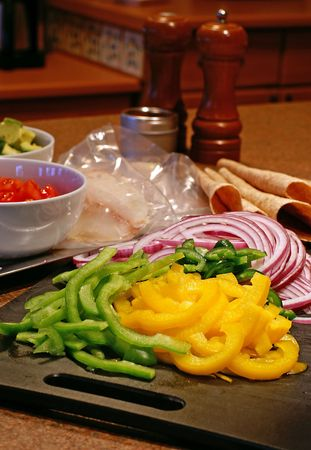 Preparing fish tacos with fresh ingredients like peppers, red onions and tomatoes.
