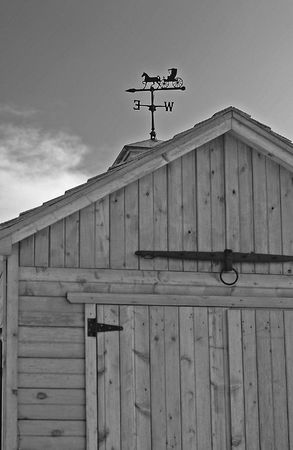 Weather vane and cupola atop a wooden carriage house or garden shed