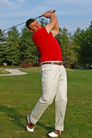 Early season golfer follows the flight of his ball down the fairway.