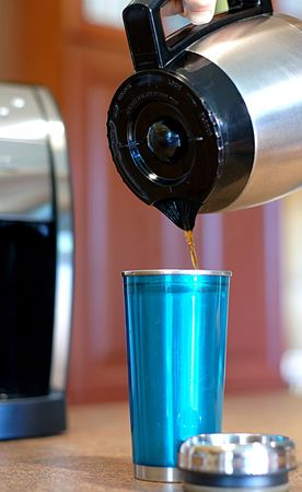 Pouring coffee into a travel mug from a carafe at home Stock Photo - 3132342