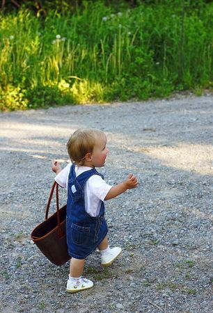 going places: Sixteen-month-old toddler carries a market bag down a country lane Stock Photo