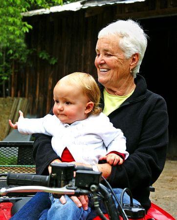 A toddler sits with her grandmother in front of a barn