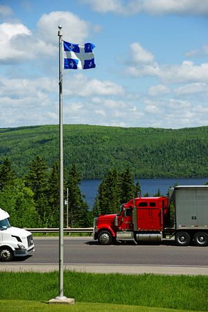 Transport trucks on the Trans Canada Highway with Quebecs flag in the foreground photo