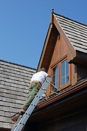 cedar shakes: Pintor en una escalera de madera en la tinci�n de un registro de casa  Foto de archivo