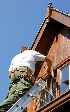 Painter on a ladder staining woodwork on log home