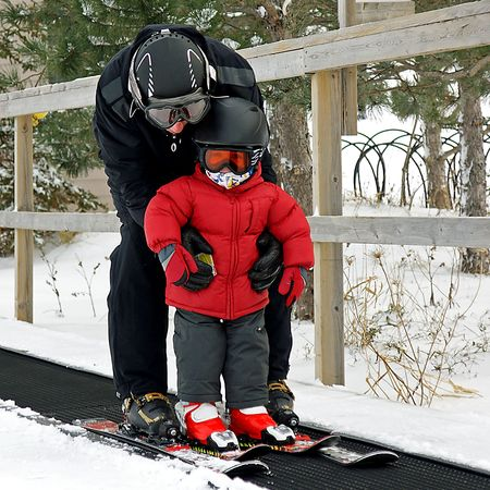 A father takes his toddler up the magic carpet on skis for the first time