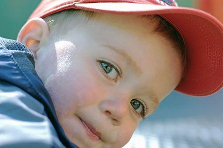 Toddler wearing a ball cap looks intently at photographer Reklamní fotografie