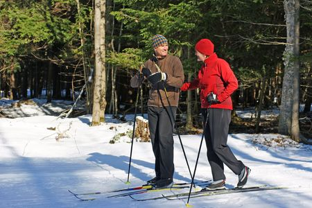 snow break: Active baby boomers on nordic skis in Ontario forest Stock Photo