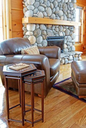 A leather chair and ottoman beside a riverstone fireplace in a log home