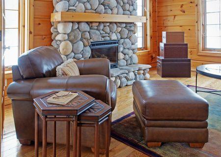 chemin�e gaz: Une chaise et ottoman en cuir � c�t� d'un Riverstone chemin�e dans une maison de bois rond Banque d'images
