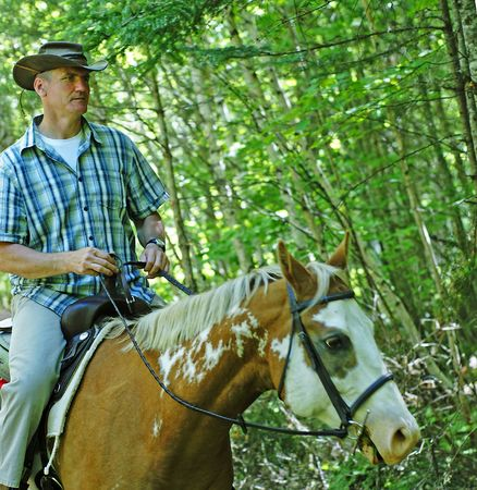 outdoorsman: Mature man out for a trail ride on an Appaloosa in a Canadian forest Stock Photo