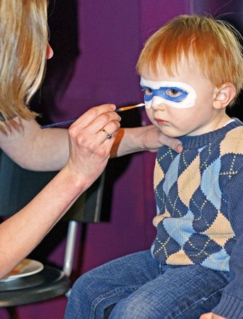 Face Painting - A little masked superhero concentrates on the task at hand.