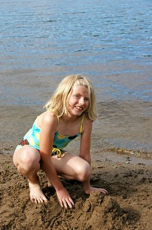 eyed: Blond Girl playing in the sand