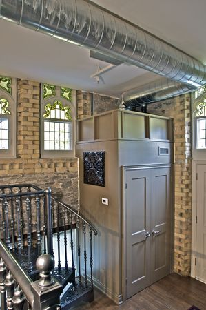 A loft conversion with architectural details such as stone walls, stained glass windows, exposed ductwork and a spiral staircase