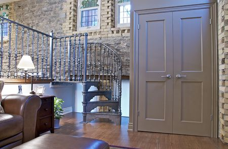 banister: A loft conversion with architectural details such as stone walls, stained glass windows, exposed ductwork and a spiral staircase