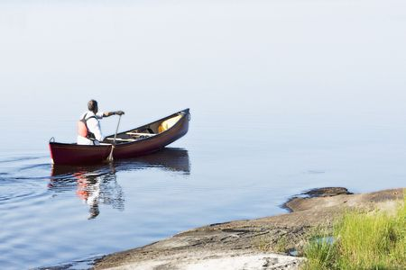 A man out for a morning paddle in a red canoe Stock Photo