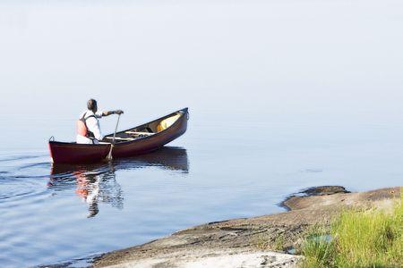 piragua: Un hombre fuera para un paddle ma�ana en una canoa rojo