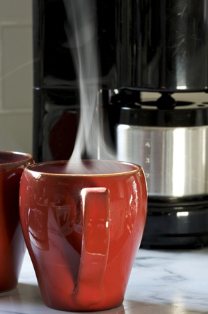 Steaming hot coffee in a red cup brewed at home saves money during an economic downturn. Stock Photo